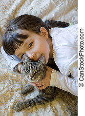 Little girl hugging her cat - A happy litte girl giving her...