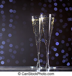 Two glasses of champagne on dark bokeh background