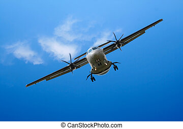 propeller airplane landing in cloudy sky - propeller...