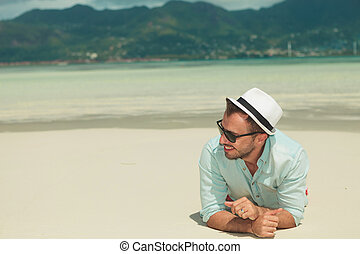 man laying down in sand on the beach looking away