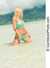 girl posing on her knees in water while looking away -...