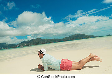 man lying down contemplating the exotic view - young man...