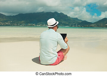 man in the sand with legs crossed reading ipad - man sitting...
