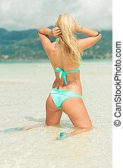 sexy woman in bikini knees down in water fixing her hair -...