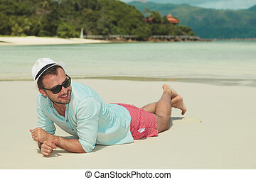 man lying in the sand with his hands crossed while looking...