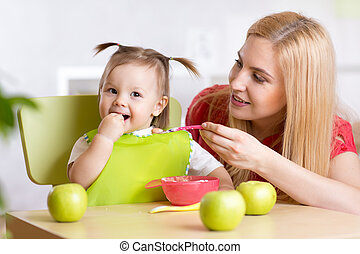 Happy Mother Feeding Baby - Mother Feeding Baby Girl with...
