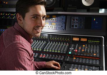 Engineer Sitting At Mixing Desk In Recording Studio