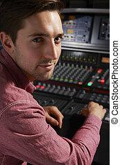 Engineeer Working At Mixing Desk In Recording Studio