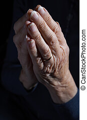 Senior Woman's Hands Clasped In Prayer