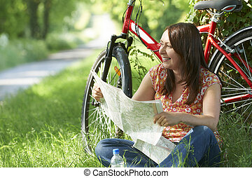 Woman On Cycle Ride Resting And Looking At Map
