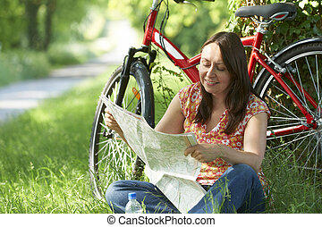 Middle Aged Woman On Cycle Ride In Countryside Reading Map