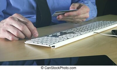Businessman using credit card for online transaction with...