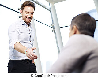 businessman reaching out for a handshake - young caucasian...