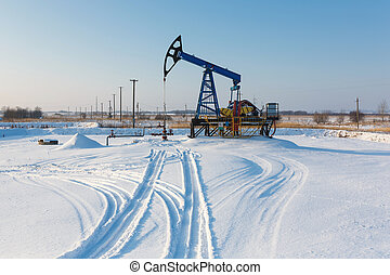 Oil derricks in winter - Oil derricks on snowy field at...
