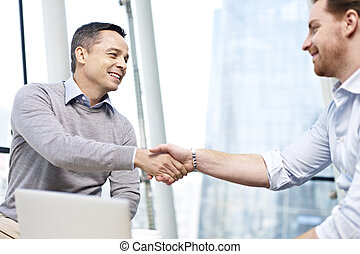 businesspeople shaking hands - two caucasian businesspeople...