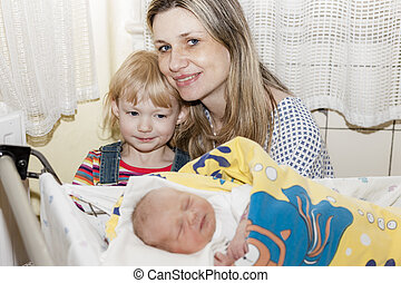 portrait of mother with her daughters in maternal hospital