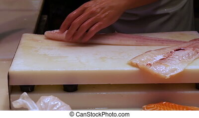 Cutting white fish on the counter
