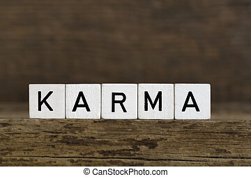Karma - The word karma written in cubes on wooden background