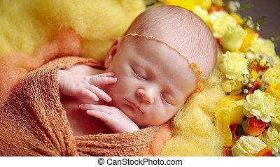 Cute little newborn baby girl sleeping in flowers