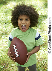 Excited Young Boy Playing American Football In Park