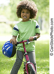 Young Boy Learning To Ride Bike In Park