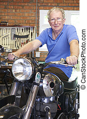 Senior man Sitting On Restored Vintage Motorcycle