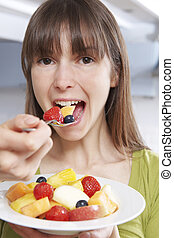 Young Woman Eating Bowl Of Fresh Fruit Salad