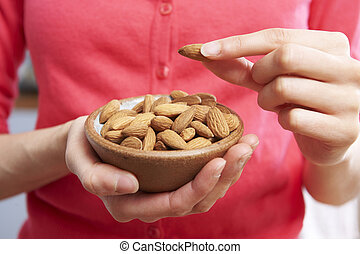 Woman Eating Healthy Snack Of Almonds