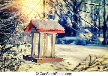 Snow covered bird feeder at sunrise Nature background - Snow...