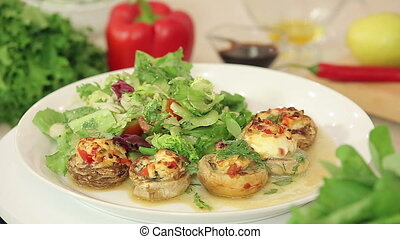 Stuffed champignon on white plate with salad, meal...