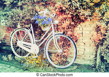 Old bicycle with flowers leaning against brick wall