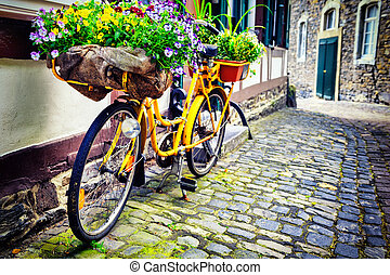 Old rusty bicycle with flowers leaning against house wall