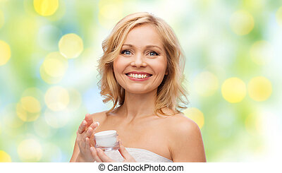 happy middle aged woman with cream jar - beauty, people,...