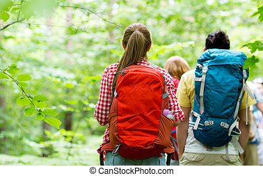 close up of friends with backpacks hiking - adventure,...
