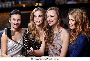 women with smartphone selfie stick at night club -...