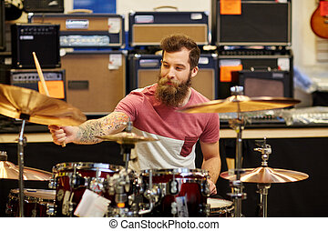 male musician playing cymbals at music store - music, sale,...