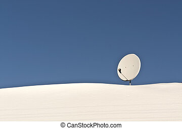 Sattelite antenna on snowy roof. Seasonal background.