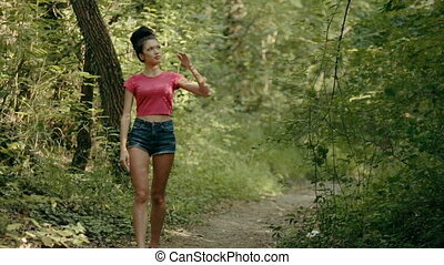 Sexy young woman walking through the woods