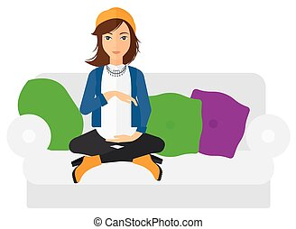 Pregnant woman sitting on sofa - A pregnant woman sitting on...