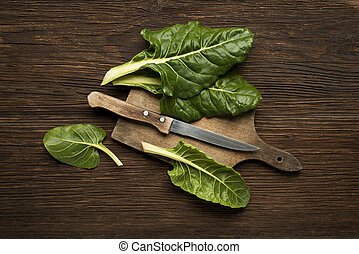 Chard - Fresh swiss chard leaves on a wooden background.