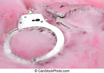 sex toy - handcuffs in a background of pink feathers