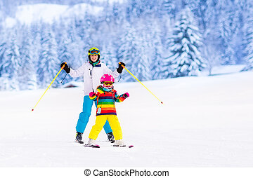 Kids skiing in the mountains - Boy and girl skiing in...