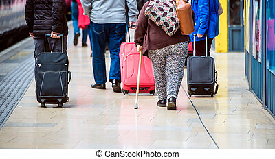 People with luggage - Travellers walk through train station...