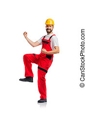 Young handsome worker in red overalls. Studio shot on white...