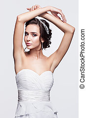 Portrait of beautiful young brunette woman bride in white...