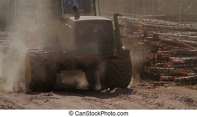 Feller Buncher drives from the forest in sawmill - Feller...