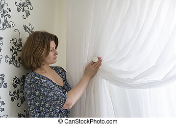 Woman hanging up his white curtains at window