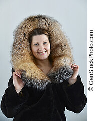 woman in a fur coat on  light background