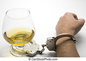 Alcohol and handcuffs - alcohol addiction concept
