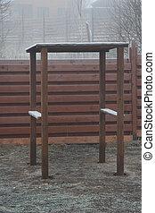 wooden shelter in a frozen garden